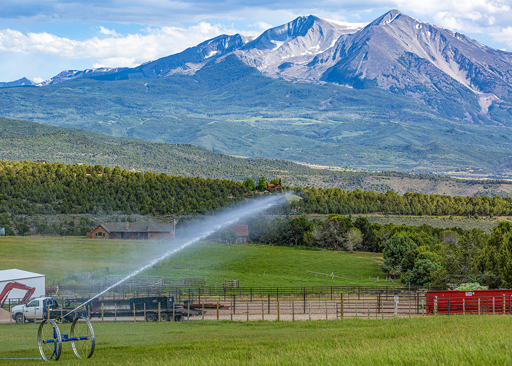 Roaring Fork Valley Ranch at the base of Mount Sopris with sprinkler watering the fields for hay; Engel & Völkers Real Estate
