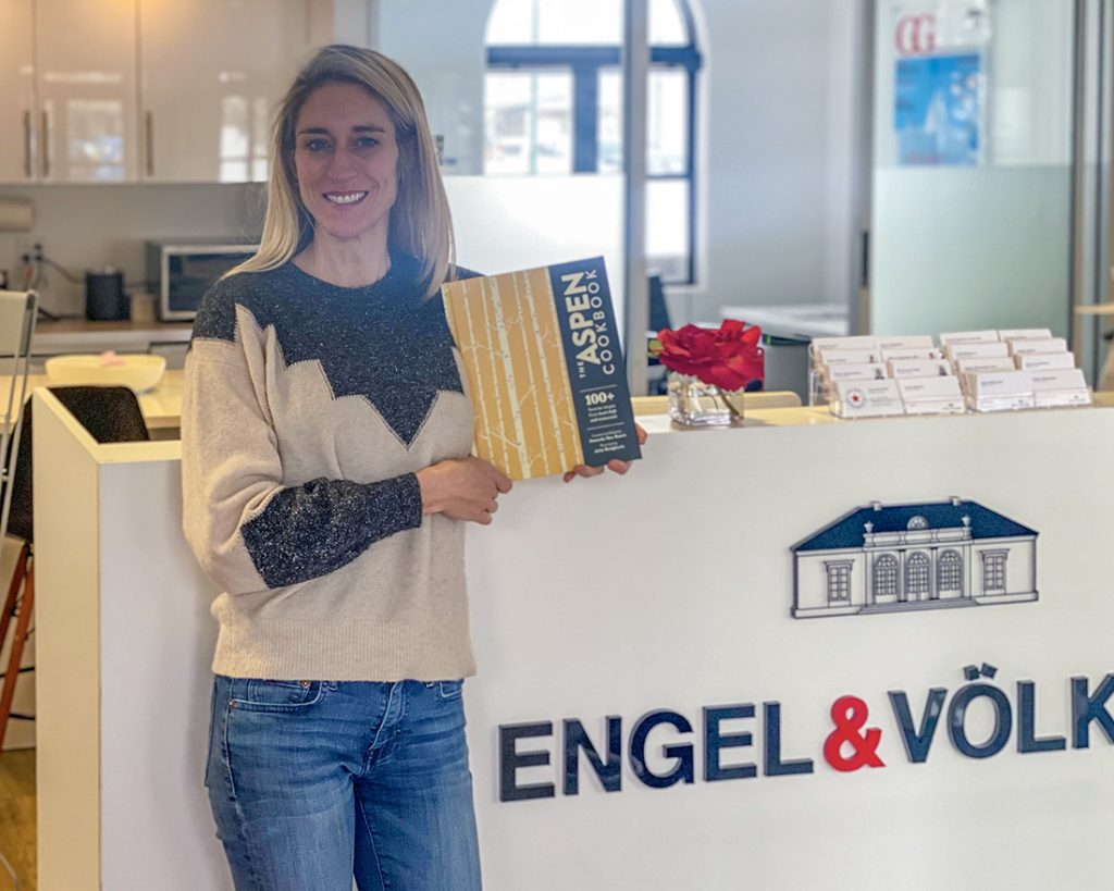 Roaring Fork Valley Real Estate Engel & Völkers Interviews Amanda Rae Busch, Curator and Editor of the Aspen Cookbook, Summer Berg, Owner of Engel & Völkers Roaring Fork Valley Holding A Copy Of The Aspen Cookbook